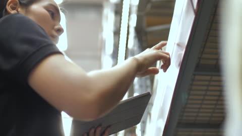 stockvideo's en b-roll-footage met vrouw werknemer controle karton vakken in distributie magazijn, close-up - merchandise