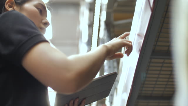 woman worker checking cardboard boxes in distribution warehouse, close-up - deposito video stock e b–roll