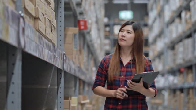 woman worker checking stock in warehouse inventory - retail manager stock videos & royalty-free footage