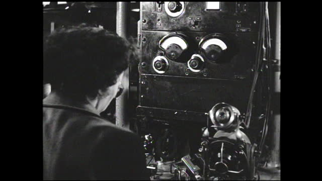 woman worker working on telephone assembly line; woman with gloves turning dials and testing handsets; busy factory floor with workers packing up... - 1940 1949 stock videos & royalty-free footage