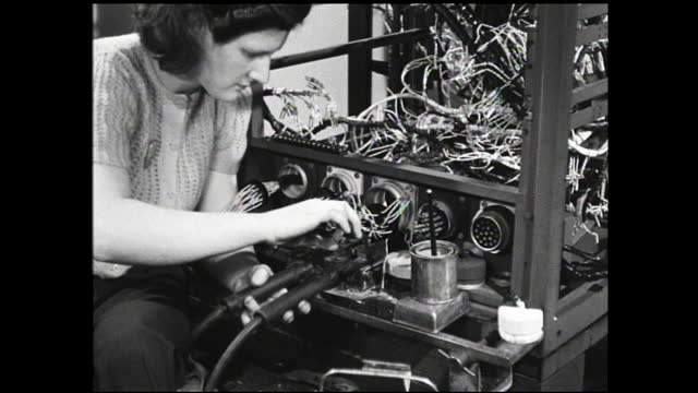 woman workers sitting in front of metal frames working on circuits and wires; close up of woman soldering wire to the connector - 1940 1949 video stock e b–roll