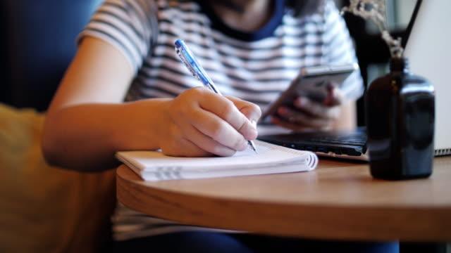 vidéos et rushes de femme travaillant et écrivant sur le cahier avec l'utilisation du téléphone portable, travaillant à la maison - stylo
