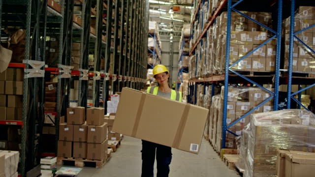 woman working at a warehouse. carrying heavy boxes - satisfaction stock videos & royalty-free footage