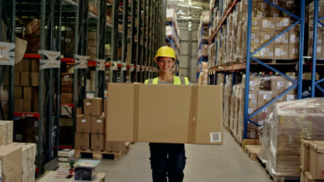 Woman working at a warehouse. Carrying heavy boxes