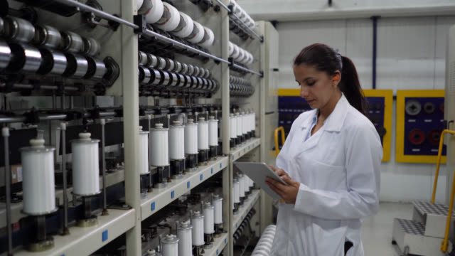 woman working at an adhesive tape factory wearing ear protectors while walking down the production line checking and holding a tablet - ear protectors stock videos and b-roll footage