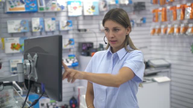 vídeos de stock, filmes e b-roll de mulher que trabalha em uma loja de eletrônicos - loja de produtos eletrônicos