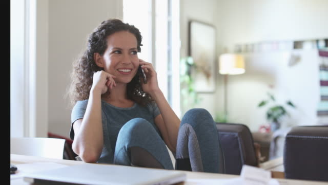 woman working at home making a phone call. - usare il telefono video stock e b–roll