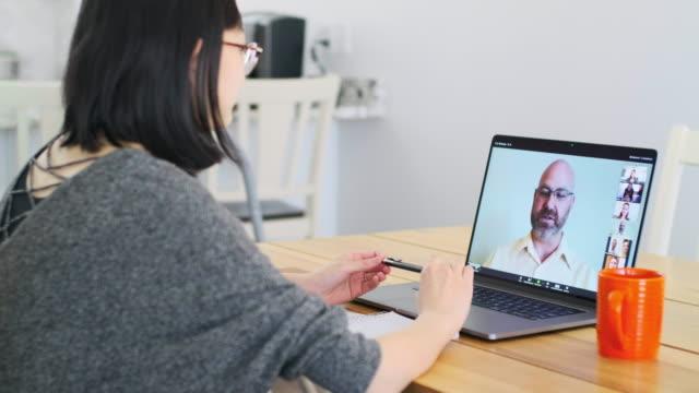 vidéos et rushes de femme travaillant à la maison sur une réunion de chat de web - visioconférence