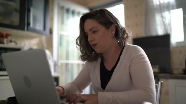 stockvideo's en b-roll-footage met vrouw die thuis werkt gebruikend laptop - online leren