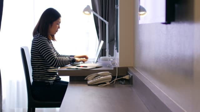 Woman working at home with her laptop on wooden desk , dolly shot right to left