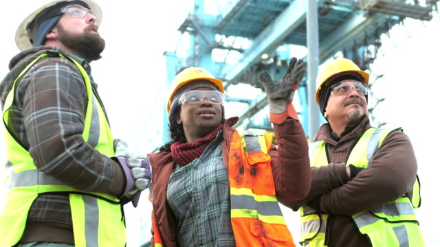 woman working at seaport, talking with co-workers - hard hat stock videos & royalty-free footage