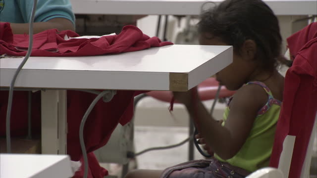 ms woman working at sewing factory with daughter playing by her table / cabimas, zulia, venezuela - clothing stock videos & royalty-free footage