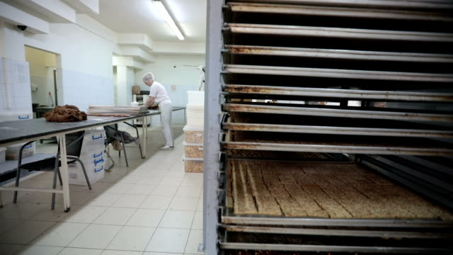 vidéos et rushes de femme travaillant à la production de boulangerie - charlotte médicale ou sanitaire