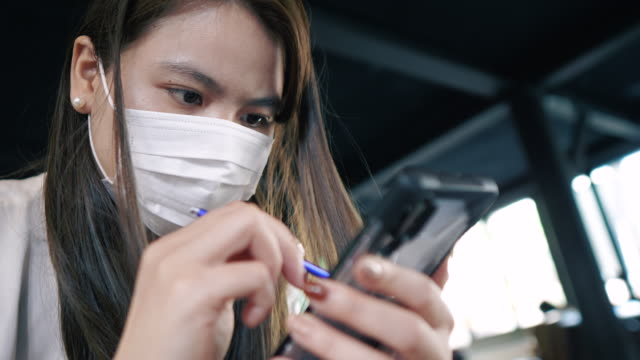 vídeos de stock e filmes b-roll de woman working by smartphone and protection from coronavirus and pm2.5 dust by mask in office/public places - china