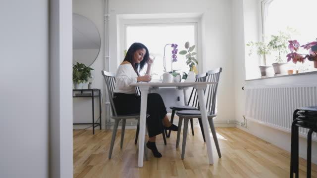vídeos y material grabado en eventos de stock de mujer trabajando desde la mesa de su comedor en casa - escandinavia