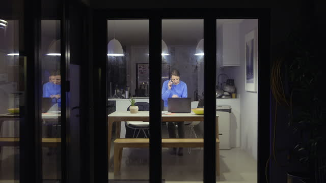woman working from home at night - dining room stock videos & royalty-free footage
