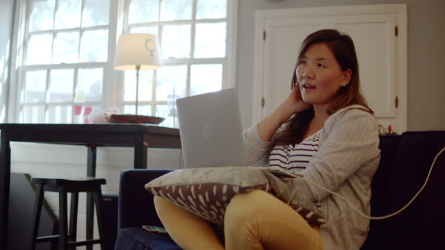 a woman, working from home, collaborates via videoconference from her home offices with a coworker - home interior stock videos & royalty-free footage