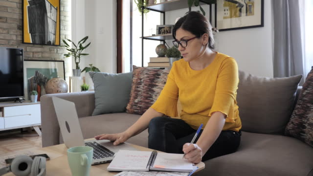 stockvideo's en b-roll-footage met vrouw die van huis aan laptop werkt en het behandelen van beursovereenkomsten - ondertekenen schrijven