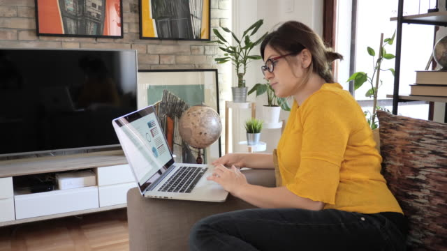 woman working from home on laptop during pandemic lockdown measures - decisions stock videos & royalty-free footage