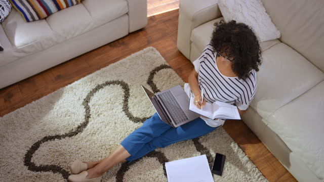 ld woman working from home sitting on the living room floor with a laptop - part of a series stock videos & royalty-free footage