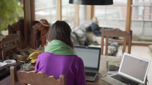 vídeos de stock, filmes e b-roll de uma mulher trabalhando em casa com seus dois tops de colo na mesa de jantar - parte de uma série