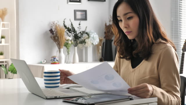 woman working from home with laptop and digital tablet - asian stock videos & royalty-free footage