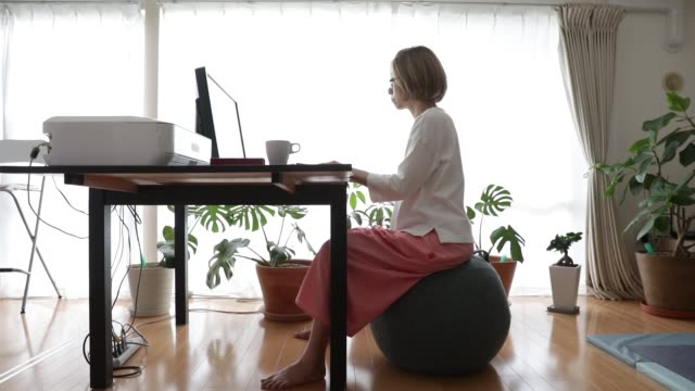 a woman working from the home. - fitness ball stock videos & royalty-free footage