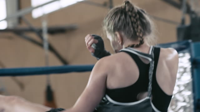 Woman working hard in boxing gym
