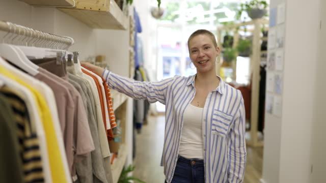 vídeos de stock e filmes b-roll de woman working in a clothing store - loja de roupa