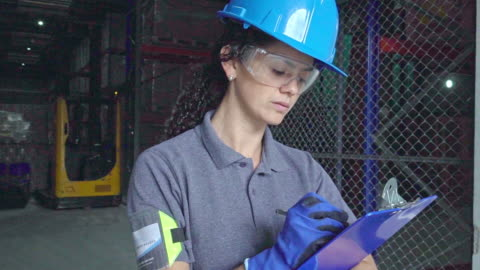 woman working in a warehouse doing inventory - examining stock videos & royalty-free footage
