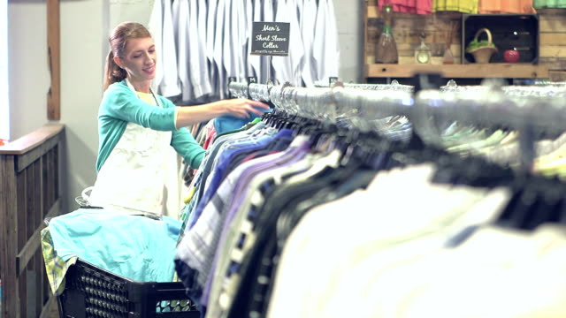 woman working in clothing store, putting clothes on rack - only mature women stock videos and b-roll footage