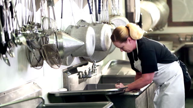 woman working in commercial kitchen washing pots - apron stock videos & royalty-free footage