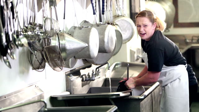 woman working in commercial kitchen washing pots - lavastoviglie video stock e b–roll