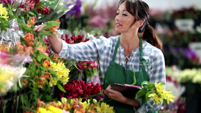 woman working in flower shop, picking blooms for bouquet - retail occupation stock videos & royalty-free footage