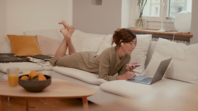 woman working in home office on couch with laptop, phone, notes - lockdown stock videos & royalty-free footage
