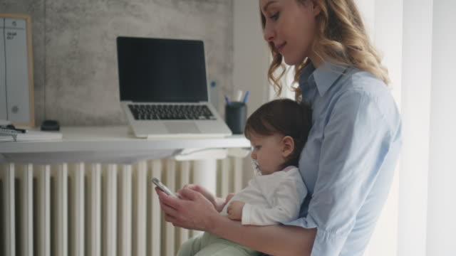 4k: woman working in home office with her baby - mother stock videos & royalty-free footage