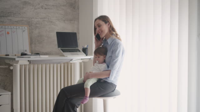 4K: Woman working in home office with her baby
