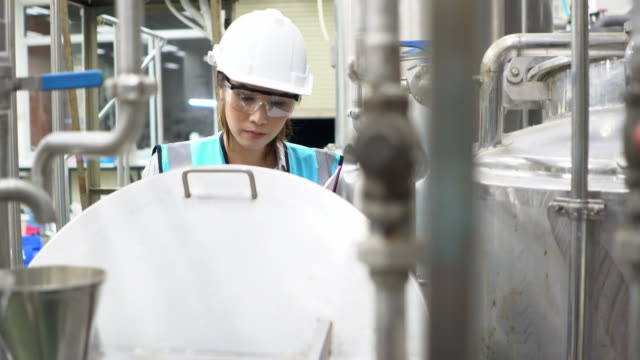 woman working in manufacturing plant - safety glasses stock videos & royalty-free footage