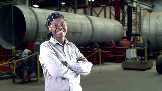 vídeos de stock e filmes b-roll de woman working in metal fabrication shop - indústria metalúrgica