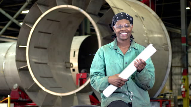 woman working in metal fabrication shop with plans - african american ethnicity stock videos & royalty-free footage
