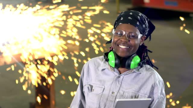 vídeos de stock e filmes b-roll de woman working in metal fabrication shop, with welder - trabalho de metal