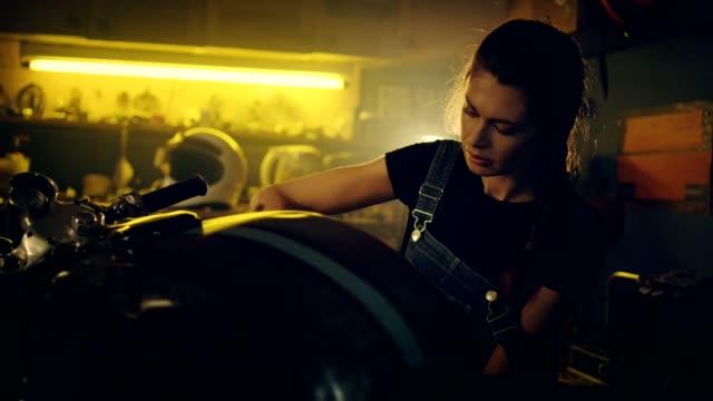 frau arbeitet in der motorradwerkstatt - werkstatt stock-videos und b-roll-filmmaterial