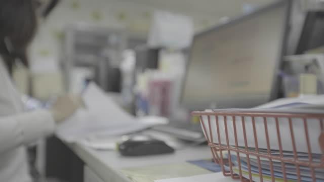 オフィスで働く女性 - ホッチキス点の映像素材/bロール