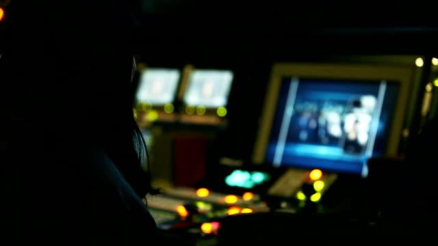 vidéos et rushes de a woman working in television broadcasting control room - salle de contrôle