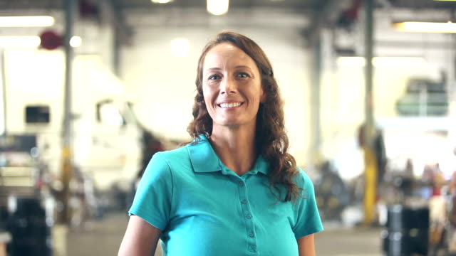 Woman working in trucking industry, smiling at camera
