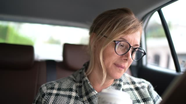 woman working inside a cab, using digital tablet and drinking coffee - portrait - reading glasses stock videos & royalty-free footage