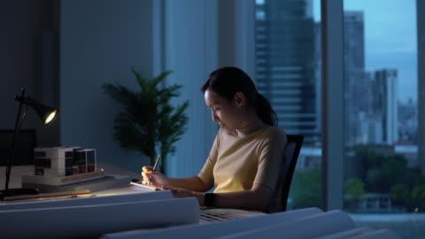 kvinna som arbetar sent på natten - koncentration bildbanksvideor och videomaterial från bakom kulisserna
