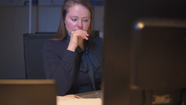 woman working late in office. - contemplation stock videos & royalty-free footage