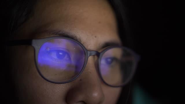 vidéos et rushes de femme travaillant sur le lit pendant la nuit - hot desking