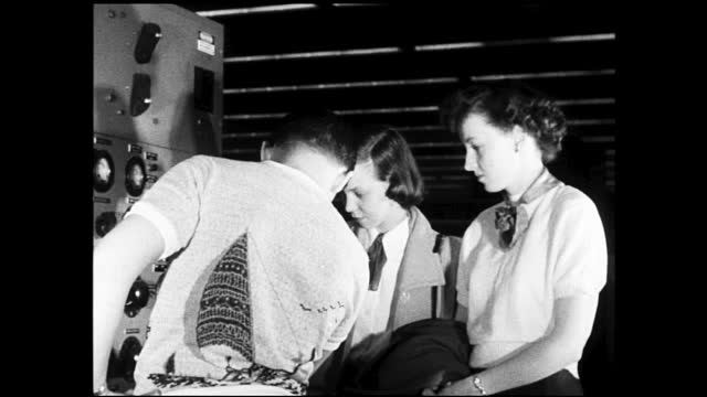 woman working on drafting table; women cutting different lengths of wires; women working on big adding machine; various workers working on different... - 1940 1949 stock-videos und b-roll-filmmaterial